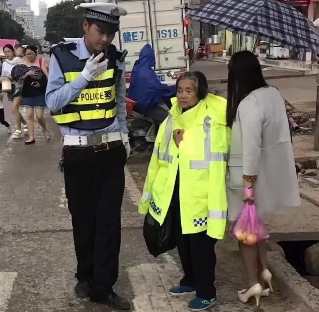 由于雨势很大,陈强便和路过的群众借了一把伞,扶着穿着 反光衣的老人